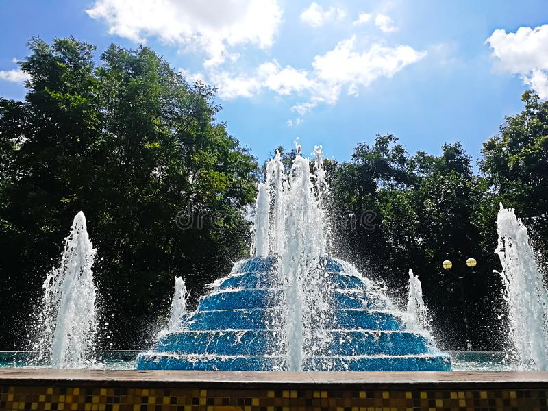 Mooie fontein op de achtergrond van bomen onder de blauwe hemel royalty-vrije stock foto