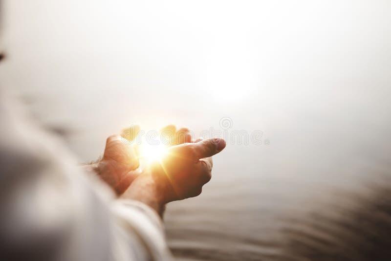 Mooie foto van Jezus Christus met hoop en licht in zijn handpalmen met een vervaagde achtergrond stock fotografie