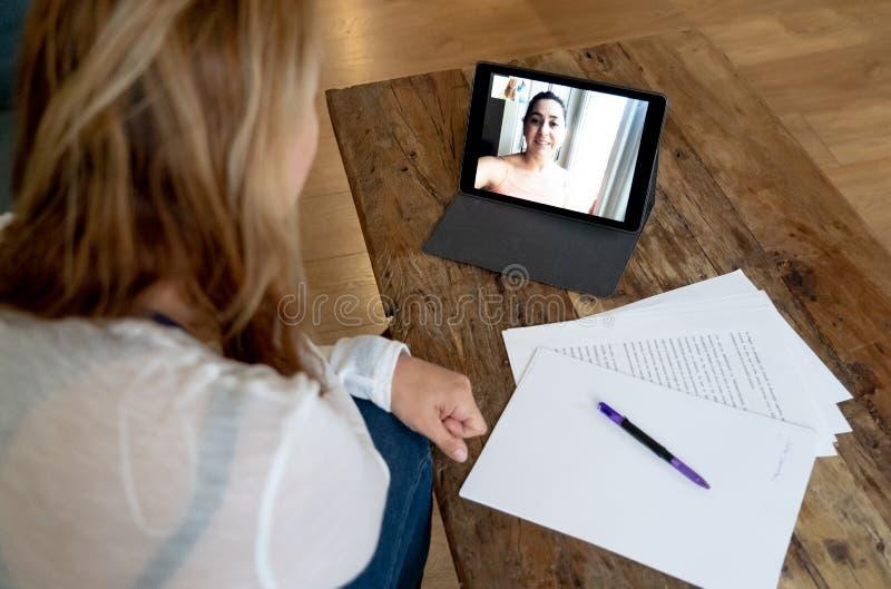 Mooie freelance vrouwenadviseur die een videoconferentievraag met online cliënt hebben thuis stock fotografie