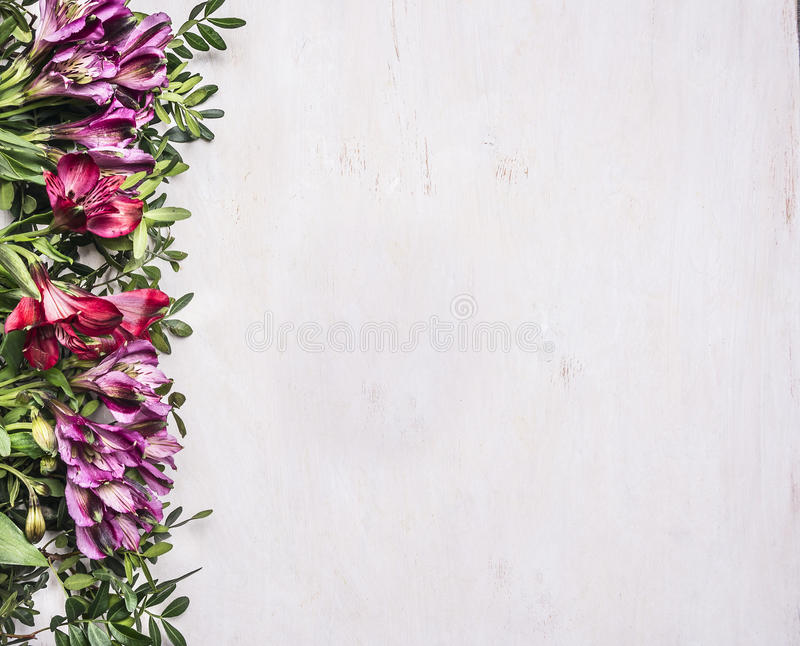 Mooie freesya multicolored bloemen met groene bladerengrens, plaats voor tekst houten hoogste mening rustieke als achtergrond stock fotografie