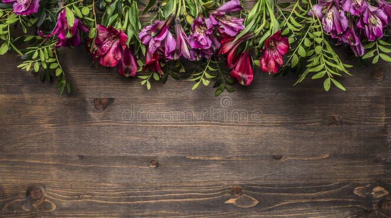 Mooie freesya multicolored bloemen met groene bladerengrens, plaats voor tekst houten hoogste mening rustieke als achtergrond royalty-vrije stock foto