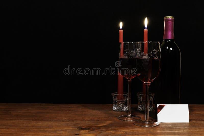 Mooie geëtste wijnglazen en fles rode die wijn, door rode kaarsen, op houten lijst met naamplaatje op donkere achtergrond worden  royalty-vrije stock afbeelding
