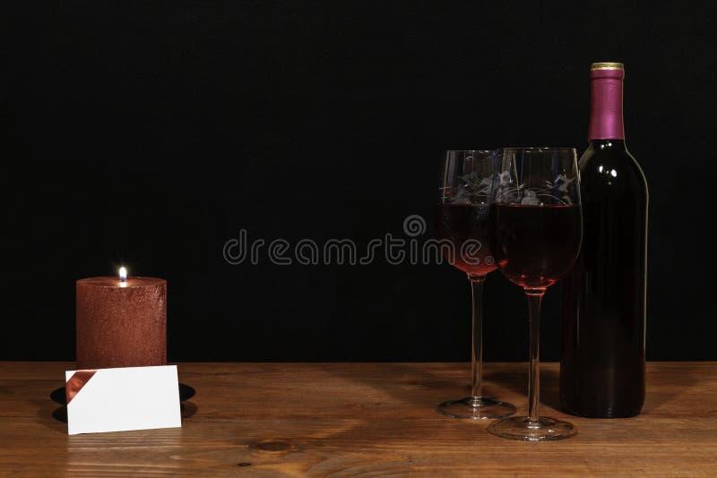 Mooie geëtste wijnglazen en fles rode wijn, rode kaars op houten lijst met naamplaatje op donkere achtergrond stock afbeelding