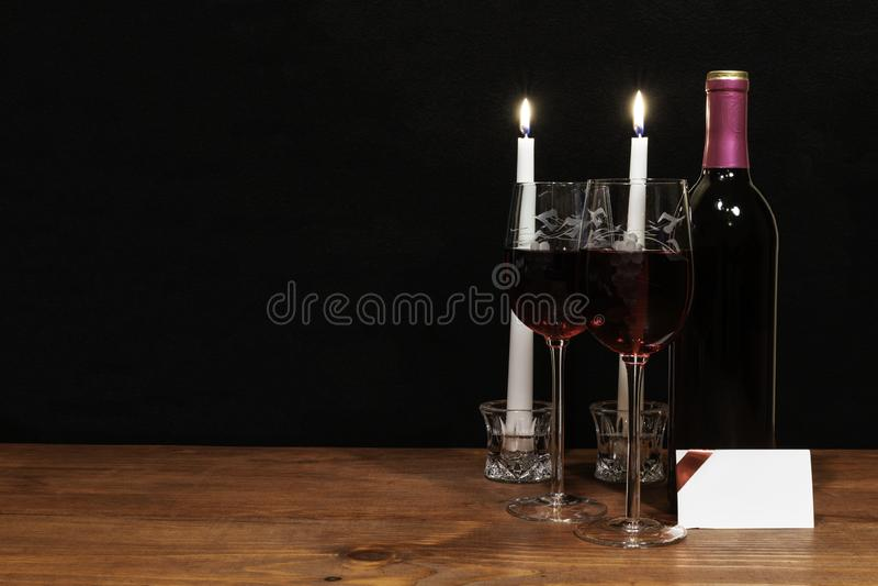 Mooie geëtste wijnglazen en fles rode wijn, witte kaarsen, op houten lijst met naamplaatje op donkere achtergrond stock fotografie
