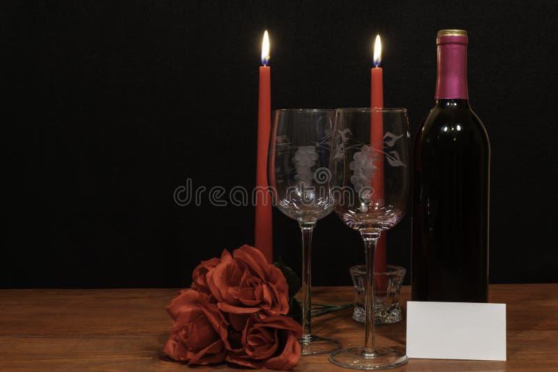 Mooie geëtste wijnglazen en fles van rode wijn, rode kaarsen en rode rozen op houten lijst met naamplaatje op donkere achtergrond stock afbeeldingen