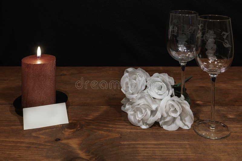 Mooie geëtste wijnglazen met awhiterozen en rode kaars en naamplaatje op houten lijst en donkere achtergrond stock foto