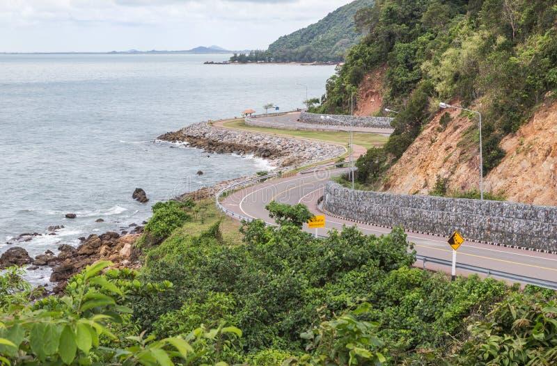 Mooie gebogen weg van Chalerm-burapa chollathit weg of toneelroute naast het overzees in Chanthaburi, Thailand stock afbeeldingen