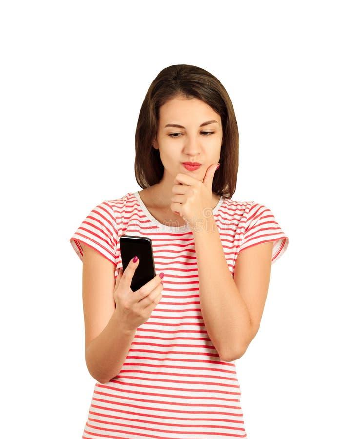 Mooie gedachte en denkende vrouw die haar mobiele telefoon controleren emotioneel die meisje op witte achtergrond wordt geïsoleer stock fotografie