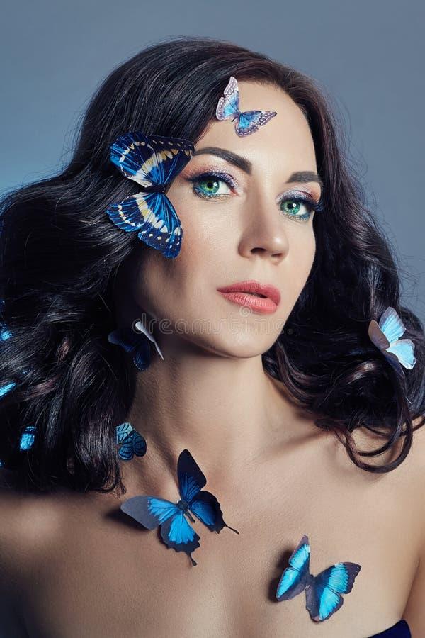 Mooie geheimzinnige vrouw met vlinders blauwe kleur op haar gezicht, brunette en document kunstmatige blauwe vlinders op de meisj stock foto