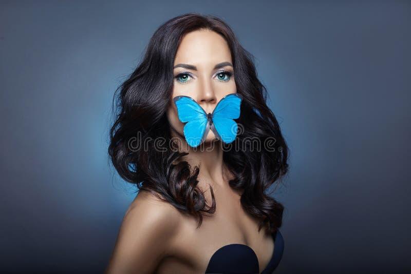 Mooie geheimzinnige vrouw met vlinders blauwe kleur op haar gezicht, brunette en document kunstmatige blauwe vlinders op de meisj royalty-vrije stock afbeeldingen