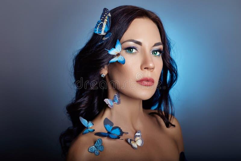 Mooie geheimzinnige vrouw met vlinders blauwe kleur op haar gezicht, brunette en document kunstmatige blauwe vlinders op de meisj royalty-vrije stock afbeelding