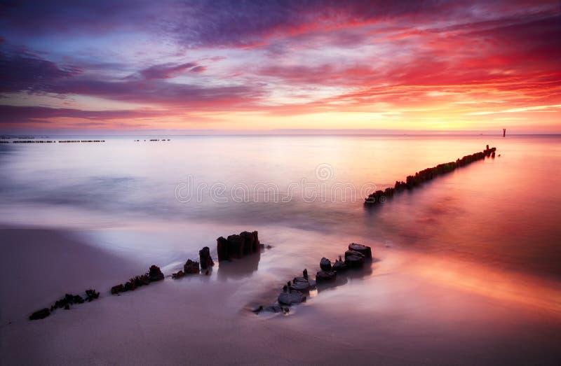 Mooie gekleurde wolken over de oceaan bij het strand bij zonsondergang stock afbeeldingen