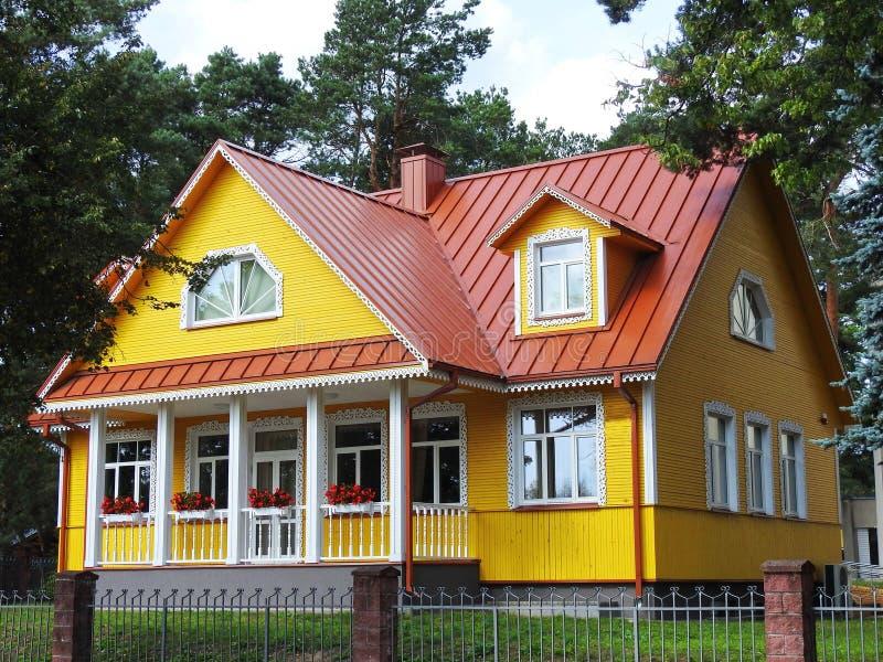 Mooie gele huis en bomen, Litouwen stock afbeelding