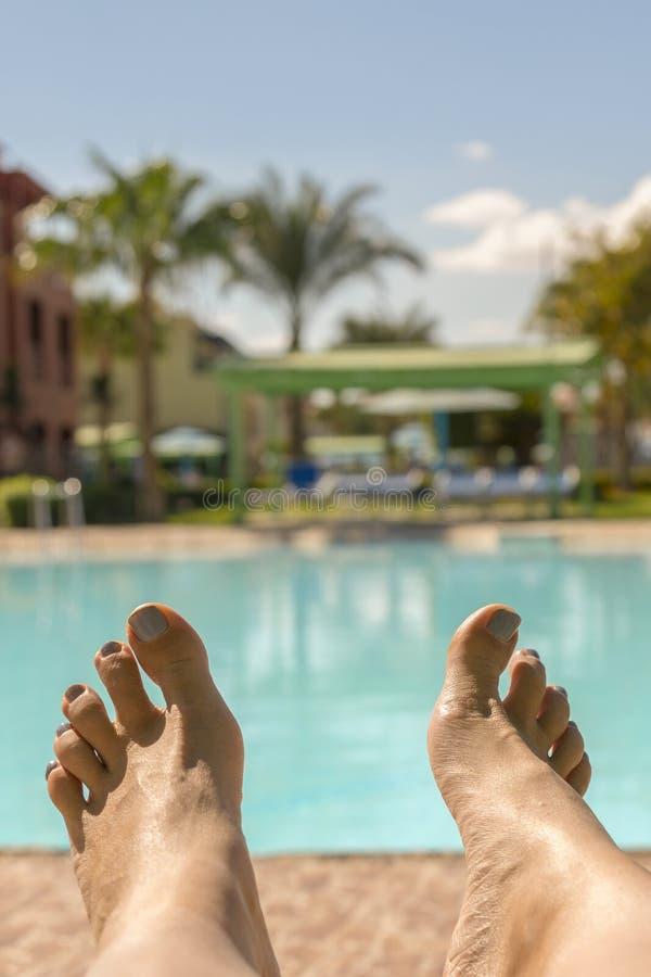 Mooie gelooide benen Close-up van vrouwelijke benen met een zwembad op de achtergrond mooie vrouwelijke benen op de achtergrond v royalty-vrije stock afbeeldingen