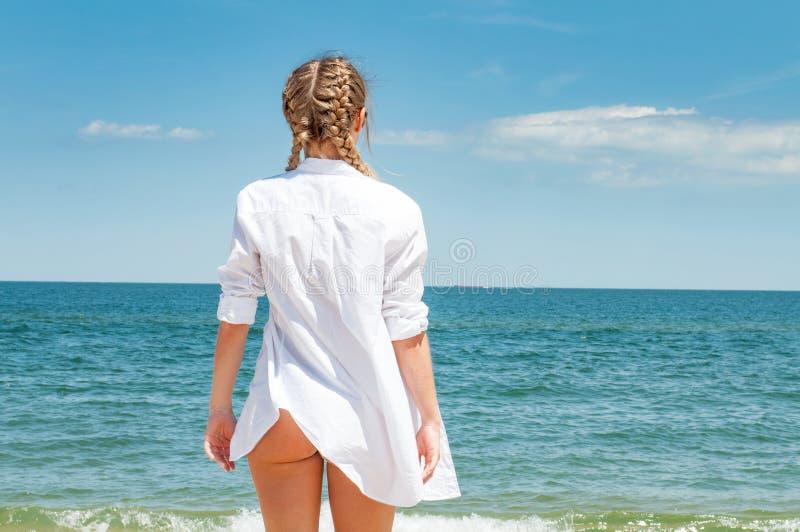Mooie gelooide vrouw die in wit overhemd oceaan, op het strand bekijken stock afbeelding