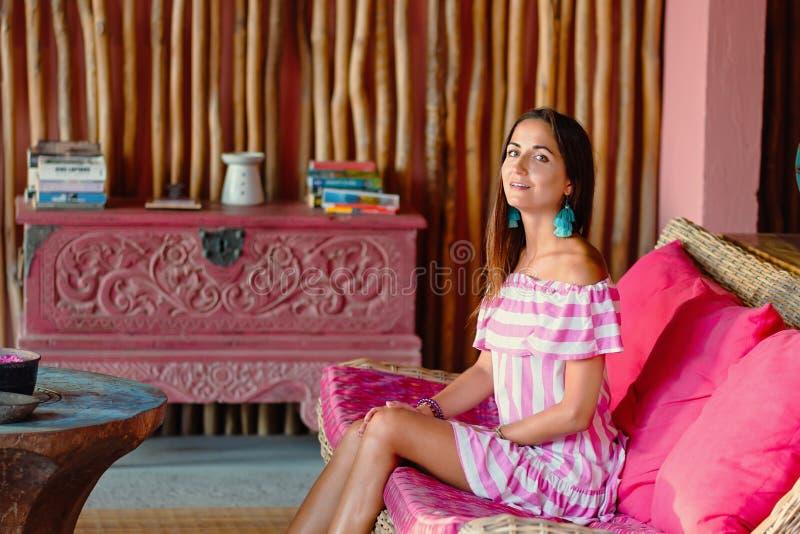 Mooie gelooide vrouw in gestreepte kledingszitting op een roze bank en het stellen Binnenland in etnische stijl Sluit omhoog royalty-vrije stock foto