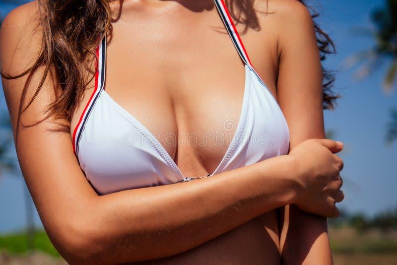Mooie gelooide vrouwelijke fitness big boobs model met een spf flesje op de borst in een stijlvol modepak royalty-vrije stock foto