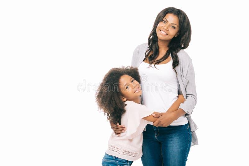 mooie gelukkige Afrikaanse Amerikaanse moeder en dochter die zich en bij camera glimlachen verenigen stock fotografie
