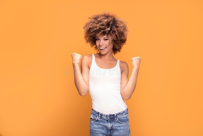 Mooie gelukkige Afrikaanse Amerikaanse vrouw het vieren overwinning stock afbeelding