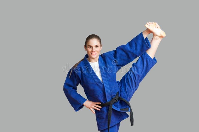 Mooie gelukkige atletische karatevrouw in blauwe kimono met zwarte stock afbeeldingen