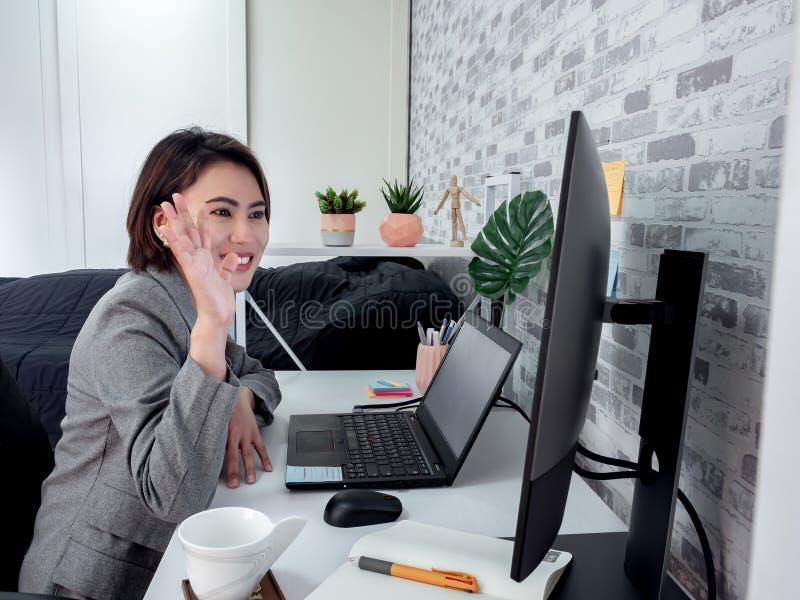 Mooie, gelukkige Aziatische vrouw die werkt met een laptop computer in haar kamer, condooms royalty-vrije stock foto