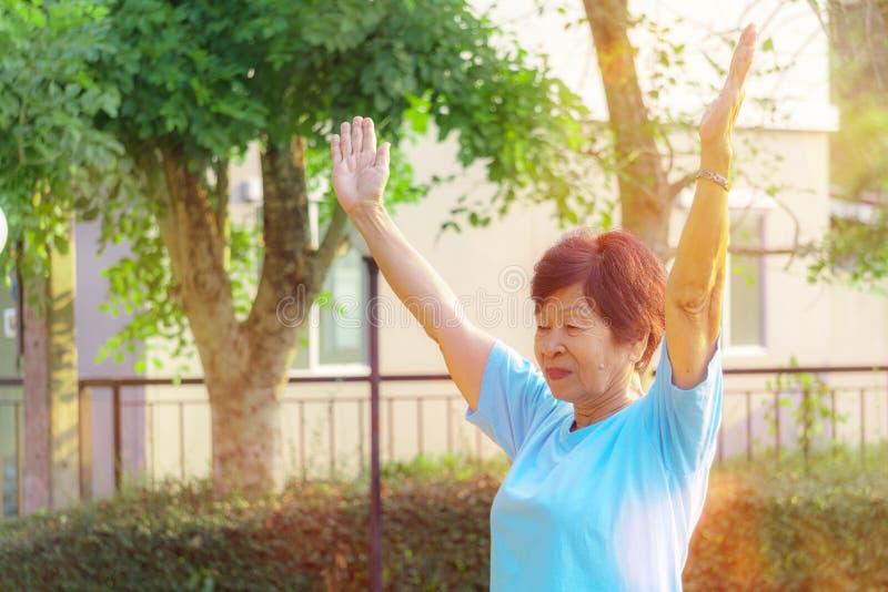 Mooie gelukkige bejaarde Aziatische vrouwenoefening in de zonneschijnochtend Oude dag, zelf-vervulling en geluk royalty-vrije stock foto's