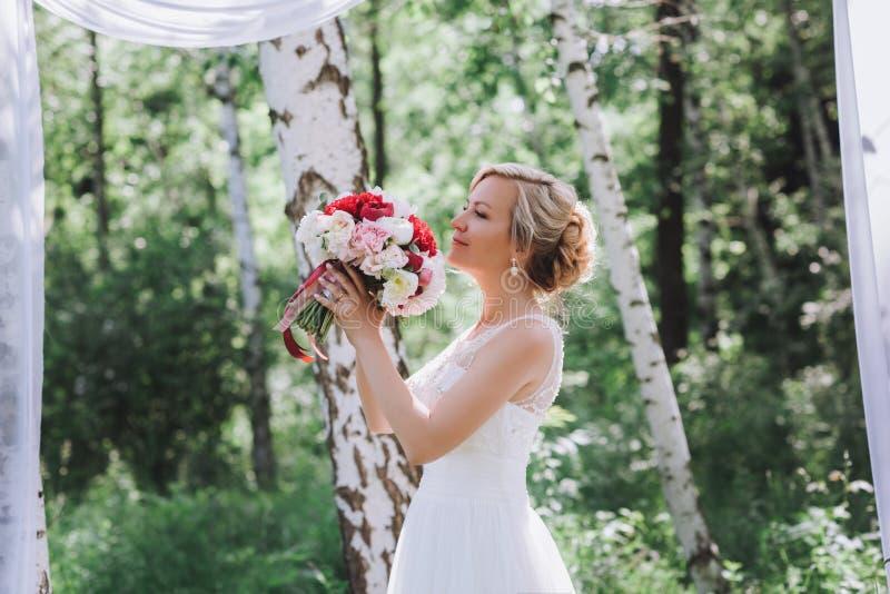 Mooie gelukkige en glimlachende bruid in huwelijkskleding die zich met een boeket van pionen in handen bevinden stock afbeeldingen
