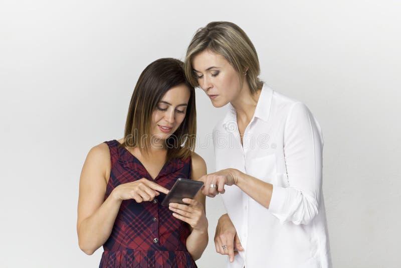 Mooie gelukkige en glimlachende vrouwelijke vriend die een smartphone gebruiken aan flirt Geïsoleerd op wit stock foto's