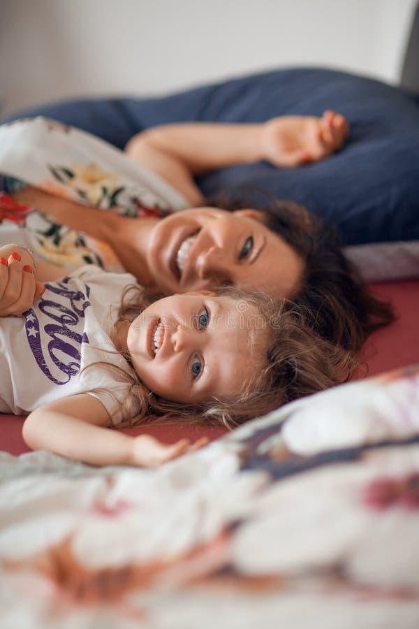 Mooie gelukkige familiescène met moeder die aan haar weinig dochter met haar pop spreken stock foto