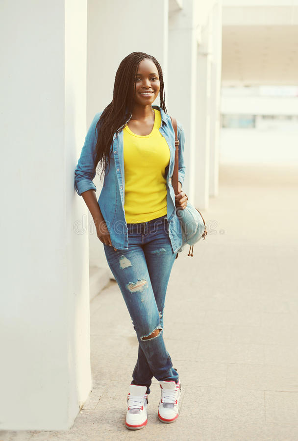 Mooie gelukkige glimlachende Afrikaanse vrouw die een jeansoverhemd dragen stock afbeelding