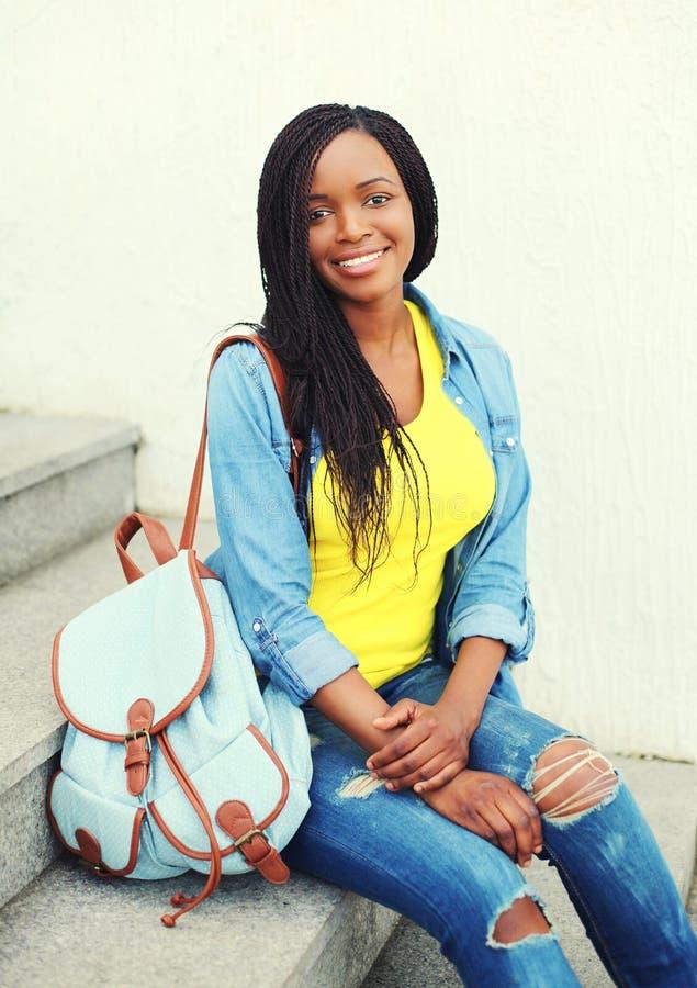 Mooie gelukkige glimlachende Afrikaanse vrouw die een jeansoverhemd met rugzakzitting draagt stock foto's