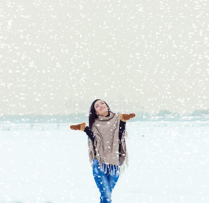 Mooie gelukkige glimlachende meisjesvrouw op een gebied op een de winteravond lopen, en gelukkige sneeuw die stock foto