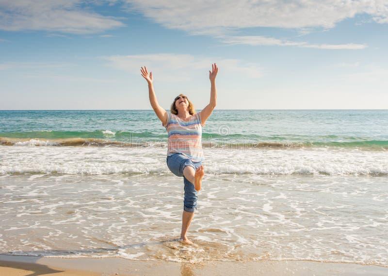 Mooie gelukkige hogere vrouw die een actieve pensioneringslevensstijl met vreugde bij het strand leven stock afbeeldingen