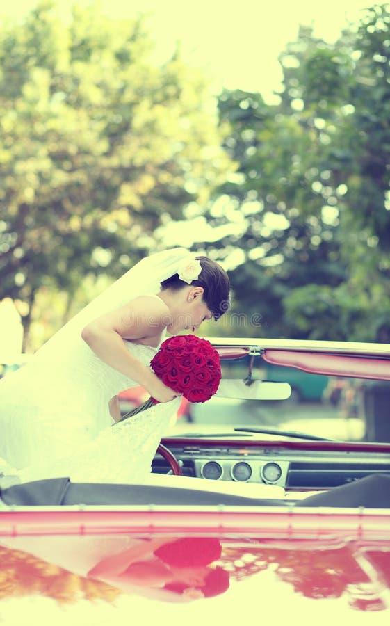 Mooie gelukkige jonge bruid die van rode retro autoauto kijken royalty-vrije stock foto's