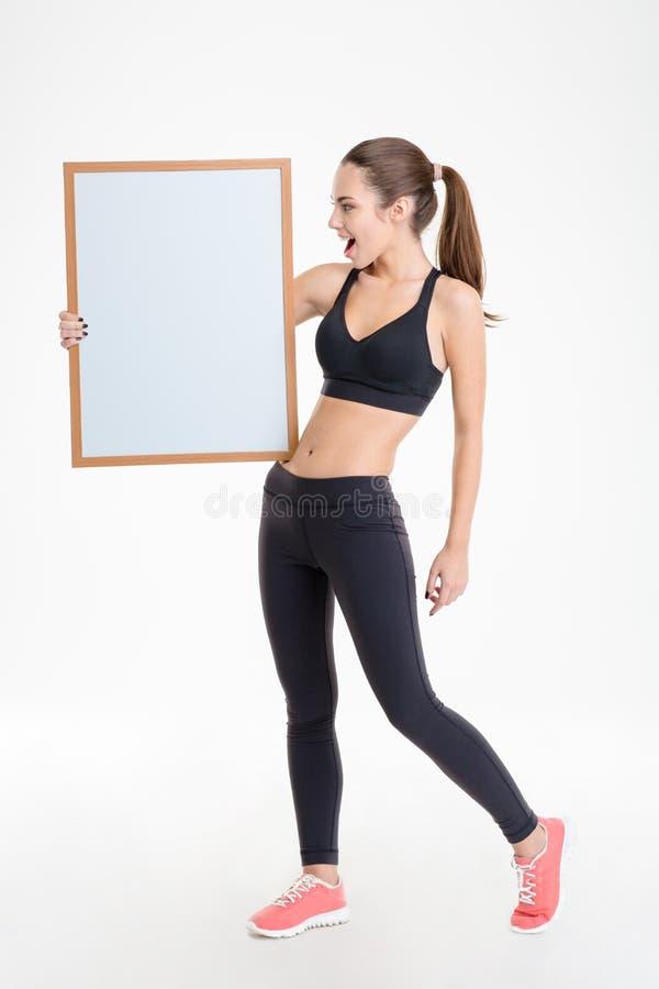 Mooie gelukkige jonge geschiktheidsvrouw in bovenkledij die lege raad tonen stock fotografie