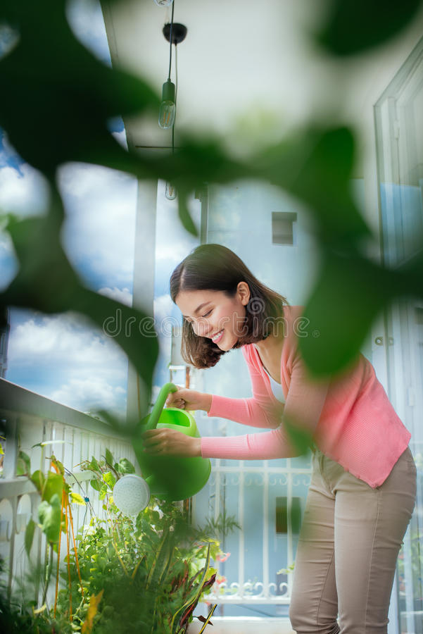 Mooie gelukkige jonge huisvrouw die de bloem thuis water geven royalty-vrije stock foto's