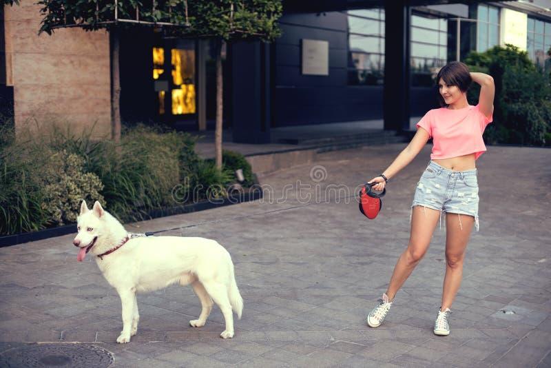 Mooie gelukkige jonge vrouw in borrels met witte schor hond royalty-vrije stock afbeelding