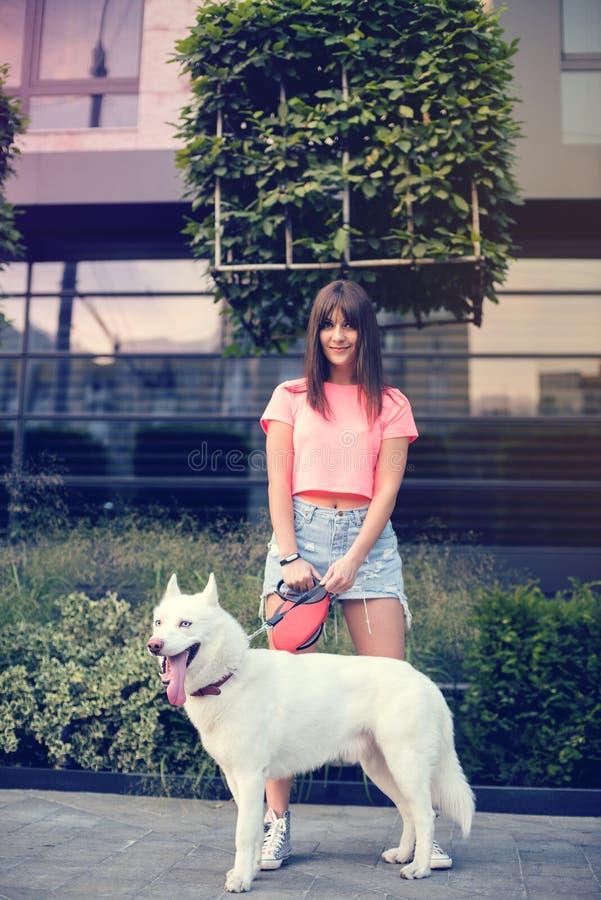 Mooie gelukkige jonge vrouw in borrels met witte schor hond stock foto