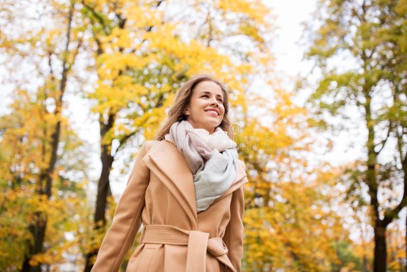 Mooie gelukkige jonge vrouw die in de herfstpark lopen stock afbeeldingen