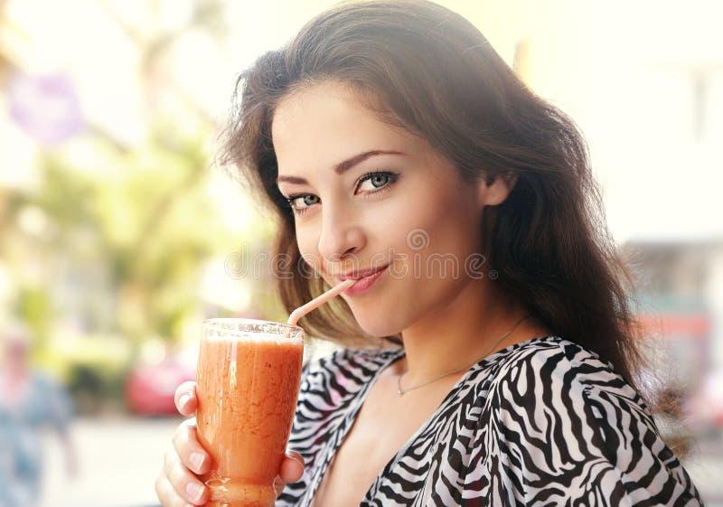 Mooie gelukkige jonge vrouw die gezond smoothiesap drinken outd stock fotografie