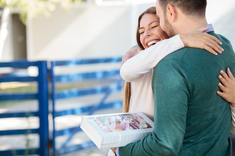 Mooie gelukkige jonge vrouw die haar vriend of echtgenoot na het ontvangen van een giftdoos koesteren stock foto