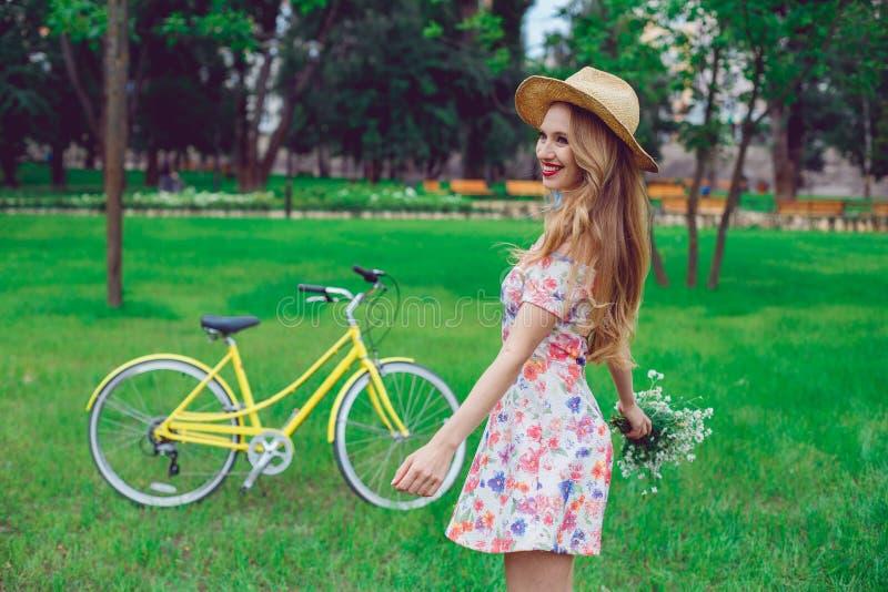 Mooie gelukkige jonge vrouw die van de zomer met wild-bloembos genieten royalty-vrije stock foto