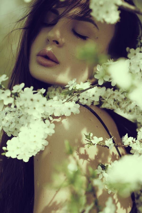 Mooie gelukkige jonge vrouw die van geur in een bloeiende de lentetuin genieten royalty-vrije stock afbeeldingen