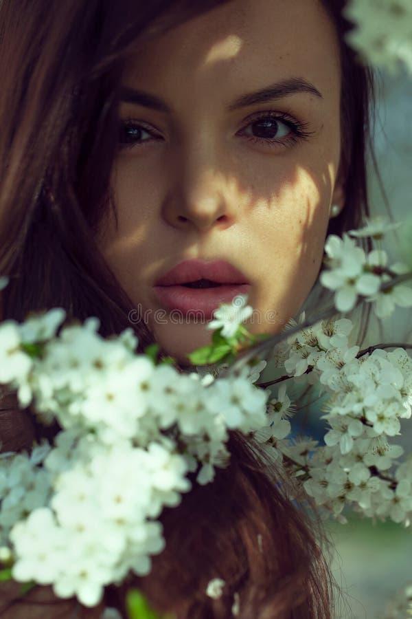 Mooie gelukkige jonge vrouw die van geur in een bloeiende de lentetuin genieten stock afbeeldingen