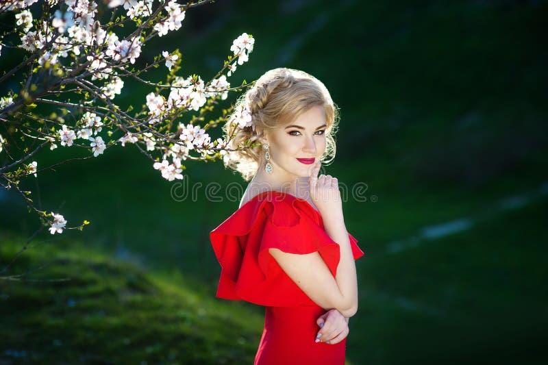 Mooie gelukkige jonge vrouw die van geur in een bloeiende de lentetuin genieten royalty-vrije stock fotografie
