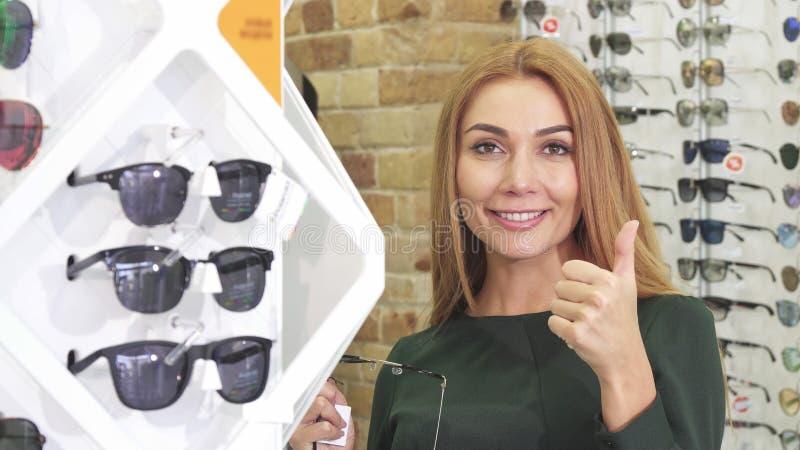 Mooie gelukkige jonge vrouw die zonnebril kiezen bij de optometristopslag stock afbeeldingen