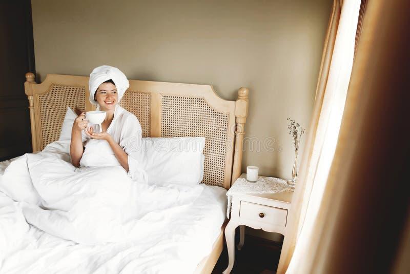 Mooie gelukkige jonge vrouw het drinken koffie en het glimlachen in bed in hotelruimte of huisslaapkamer Modieus donkerbruin meis stock fotografie