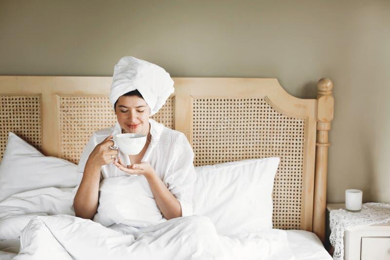 Mooie gelukkige jonge vrouw het drinken koffie of thee in bed in hotelruimte of huisslaapkamer Modieus donkerbruin meisje in witt royalty-vrije stock foto's
