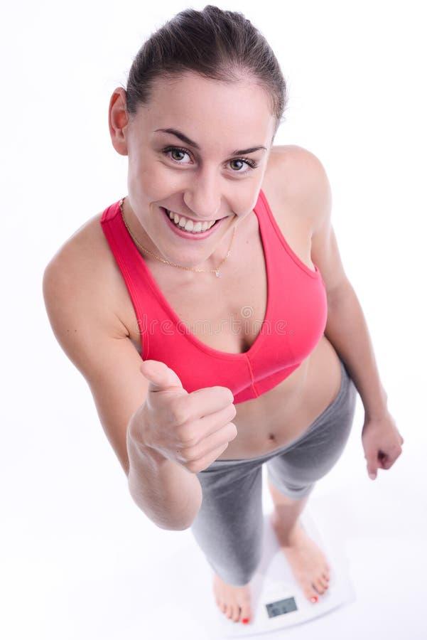 Mooie gelukkige jonge vrouw met het verlies van het het succesgewicht van de gewichtsschaal royalty-vrije stock afbeelding