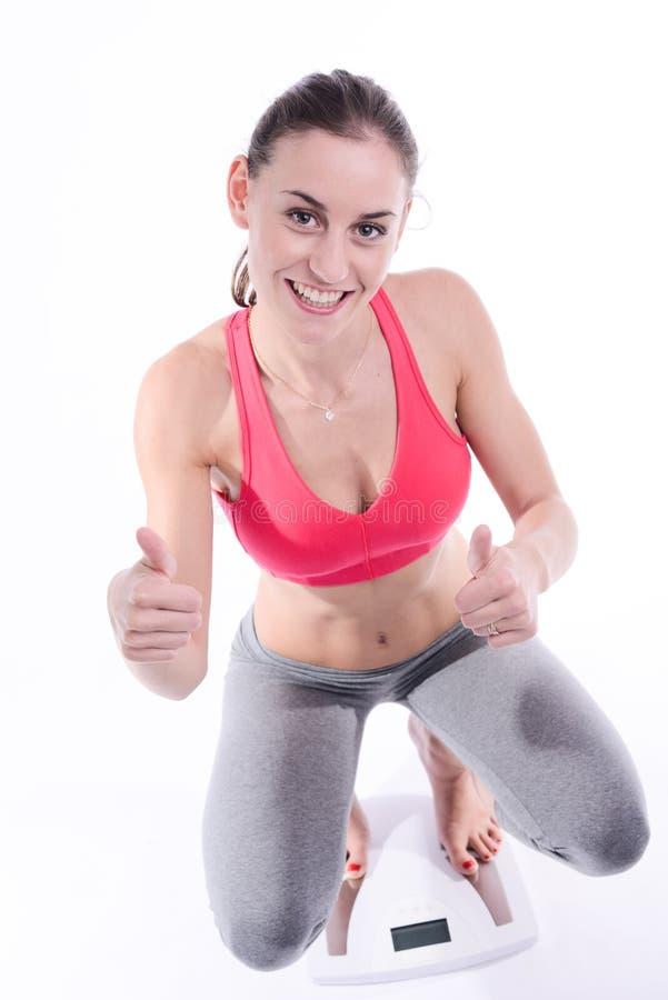 Mooie gelukkige jonge vrouw met het verlies van het het succesgewicht van de gewichtsschaal royalty-vrije stock afbeeldingen